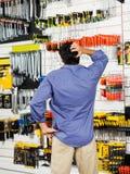 Den förvirrade kunden som skrapar huvudet i maskinvara, shoppar arkivbilder