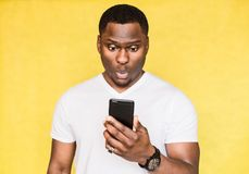 Den förvirrade och bekymrade stiliga afrikansk amerikanmannen rymmer smartphonen, stirrar med förvånat uttryck arkivbilder