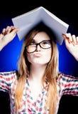 Förvirrad och förbryllad hållande skrivbok för ung flicka på henne som är head Royaltyfri Foto