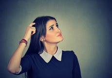 Den förvirrade tänkande kvinnan förbryllade att skrapa head sökanden en lösning Royaltyfria Foton