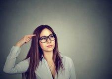 Den förvirrade tänkande kvinnan förbryllade att skrapa head sökanden en lösning Arkivfoton