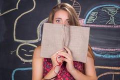 Den förvirrade unga studentflickan döljer bak en bok Royaltyfria Foton