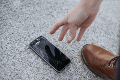 Den f?rargade unga mannen sitter och rymmer en bruten smartphone med en sprucken exponeringsglassk?rm royaltyfri bild