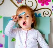 Den f?rtjusande litet barnflickan borstar hennes t?nder i pyjamas bakgrund suddighetdde den skyddande pillen f?r maskeringen f?r  royaltyfri bild