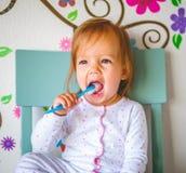 Den f?rtjusande litet barnflickan borstar hennes t?nder i pyjamas bakgrund suddighetdde den skyddande pillen f?r maskeringen f?r  royaltyfri foto
