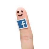 Den Facebook logoen skrivev ut på papper och klibbade till fingret Royaltyfri Foto
