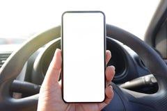 den falska övre telefonen för chaufförhandinnehavet i den tomma klara skärmen för bilen för text annonserar kopia-utrymme bakgrun arkivbilder