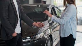 Den Famale handen ger upp tangenter f?r en bil till den manliga handen i slutet f?r bil?terf?rs?ljaren Oigenk?nnlig automatisks?l arkivfilmer