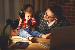 Den familjfadern och sonen behandla som ett barn att lyssna till musik med hörlurar Royaltyfri Fotografi
