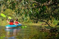 Den familjkayaking, modern och barnet som paddlar i kajak på flodkanoten, turnerar, den aktiva sommarhelgen och semestern, sporte arkivfoton