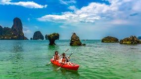Den familjkayaking, modern och dottern som paddlar i kajak p? den tropiska havskanoten, turnerar n?ra ?ar och att ha rolig aktiv  royaltyfria bilder