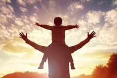 Den familjtidfadern och sonen håller ögonen på solnedgången arkivfoton