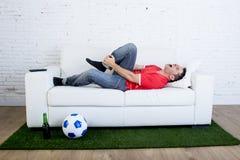 Den fanatiska fotbollsfan som ligger på soffasoffan med bollen på matta för grönt gräs som tävlar med graden för fotbollstadion s Arkivbilder