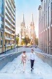 Den fantastiska kärlekshistorien av den härliga unga älska brunettmannen och kvinnan, omfamning på en stad går och att gå på soln arkivbilder