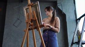 Den fantastiska konstnären drar en målning i en studio lager videofilmer