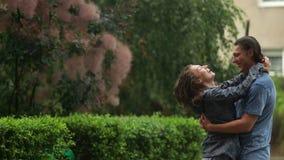 Den fantastiska kvinnan med lockigt hår och det charmiga leendet som kramar den stiliga mannen under regnigt väderanseende i stad arkivfilmer