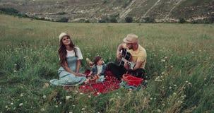 Den fantastiska picknicken med en familj, i mitt av naturen, mannen spelar på gitarren stock video