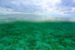 Den fantastiska sikten på båda över - bevattna sutface och under vattenyttersidavärlden Fantastiska naturbakgrunder Royaltyfria Bilder