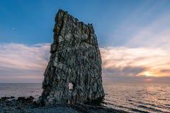 Den fantastiska solnedgången nära seglar vaggar i Ryssland Royaltyfria Foton
