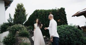 Den fantastiska unga kvinnan med långt hår och får ner trappan från trädgårds- och möter hennes pojkvän, och de är kramar arkivfilmer