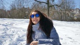 Den fantastiska vuxna flickan i blå spegelförsedd solglasögon och rakt kasta för mörkt hår kastar snöboll att spela med något uto lager videofilmer