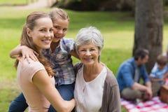 Den farmormodern och dottern med familjen i bakgrund på parkerar Arkivbilder
