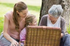 Den farmormodern och dottern med picknickkorgen på parkerar Arkivbild