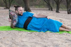 Den fascinerade stiliga mannen för transsexuellen med utgör, hårbullen som ligger på sand i blå kimono arkivbild