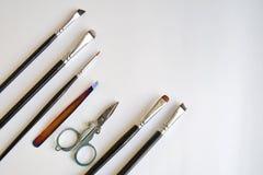 Den fastställda hjälpmedelsminkkonstnären en uppsättning av olika borstar för makeupkonstnär och sax ligger diagonalt på en vit b arkivfoton