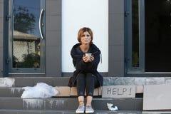 Den fattiga kvinnan med rånar att tigga och att fråga för hjälp royaltyfri foto
