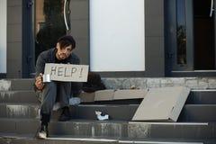 Den fattiga mannen med rånar att tigga och att fråga för hjälp royaltyfria foton