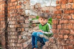 Den fattiga och olyckliga föräldralösa pojken och att sitta på fördärvar och fördärvar av en förstörd byggnad Arrangerat foto arkivbilder