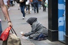 Den fattiga tiggarekvinnan sitter på trottoaren Royaltyfria Foton