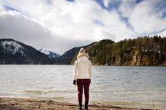 Den Feamle turisten tycker om sikten av sjön Alpsee som lokaliseras nära Hohenschwangau och Neuschwanstein slottar bavaria german arkivfoton