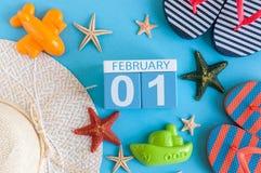 Den Februari 1st bilden av den februari 1 kalendern med sommarstrandtillbehör och handelsresanden utrustar på bakgrund Vintern gi Royaltyfria Foton