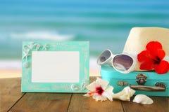 Den Fedora hatten, solglasögon, den tropiska hibiskusblomman bredvid tom ram över trätabellen och stranden landskap bakgrund Royaltyfri Fotografi