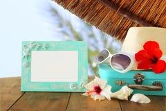 Den Fedora hatten, solglasögon, den tropiska hibiskusblomman bredvid tom ram över trätabellen och stranden landskap bakgrund Royaltyfria Bilder