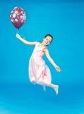 Den felika härliga flickan i rosa färger klär flyg med ballongen Arkivfoto
