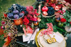 Den festliga brölloptabellen med röda höstsidor bröllop för band för inbjudan för blomma för elegans för bakgrundsgarneringdetalj Royaltyfri Bild