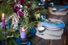Den festliga tabellinställningen med den blommabuketten, stearinljus och efterrätten royaltyfri fotografi