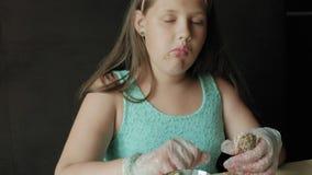 Den feta flickan som äter ivrigt en hamburgare, begrepp av ett sunt, bantar arkivfilmer