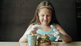 Den feta flickan som äter ivrigt en hamburgare, begrepp av ett sunt, bantar stock video
