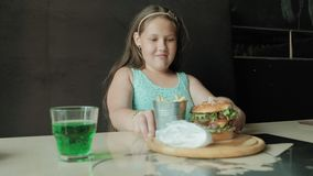 Den feta flickan som äter ivrigt en hamburgare, begrepp av ett sunt, bantar lager videofilmer