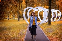 Den feta flickan som går i hösten, parkerar royaltyfri bild