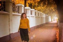 Den feta flickan som går i hösten, parkerar royaltyfria foton
