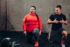 Den feta kvinnan med den personliga instruktören som att göra sitter, ups på idrottshallen arkivfoto