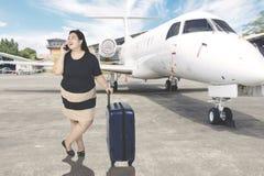 Den feta kvinnan talar på telefonen i flygplats Fotografering för Bildbyråer