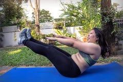 Den feta kvinnan V sitter upp övningen för begrepp för förlust för absmuskelvikt Arkivfoto