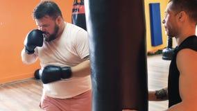 Den feta mannen i handskar slår den stansa påsen i idrottshall Förlust för individuell vikt borrar för fyllig grabb Den boxas utb arkivfilmer
