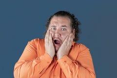 Den feta mannen i orange skjorta rymmer hans händer över hans framsida på blå bakgrund Han är mycket förskräckt arkivbild